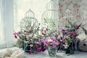 Flower arrangements in tree bird cages